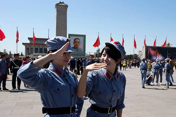 Chinese girls dressed to look like Chinese Red Army soldiers salute for a friend taking photos on Tiananmen Square on the eve of May Day in Beijing.