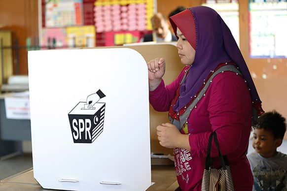 A Malaysian voter casts her ballot during the early voting for the general election in Kuala Lumpur.