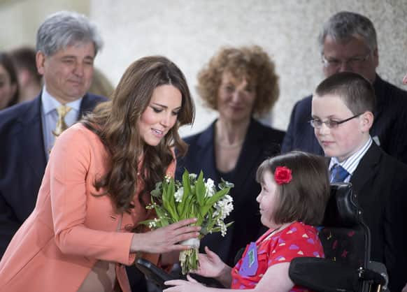 Kate, the Duchess of Cambridge, left, is presented with a bouquet of flowers by Sally Evans as she arrives for an official visit to Naomi House near Winchester, England.