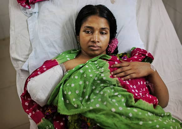 A Bangladeshi garment worker who was rescued from a building that collapsed Wednesday lays in a hospital bed with an amputated arm sustained when she was trapped inside, in Savar, near Dhaka.