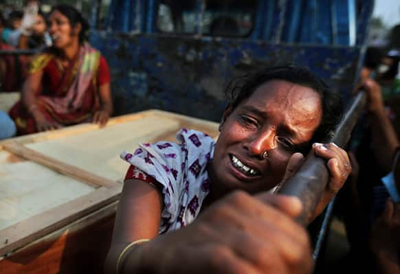 A Bangladeshi woman weeps as she sits next to the coffin of a relative who died in a building that collapsed Wednesday in Savar, near Dhaka.