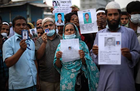 Relatives of missing victims gather holding photographs of their loved ones at the site of the garment factory building that collapsed Wednesday in Savar, near Dhaka.