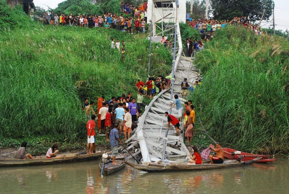 Thai villagers and rescuers look for survivors under the wreckage of a suspension bridge crossing the Pasak river after it collapsed, in Ayutthaya province, central Thailand.