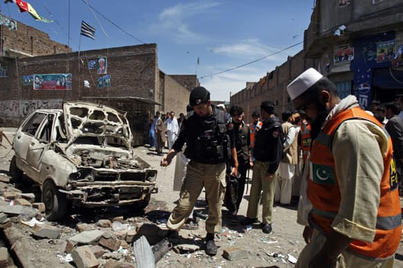Pakistani police officers and volunteers visit the site of an explosion in Peshawar, Pakistan.