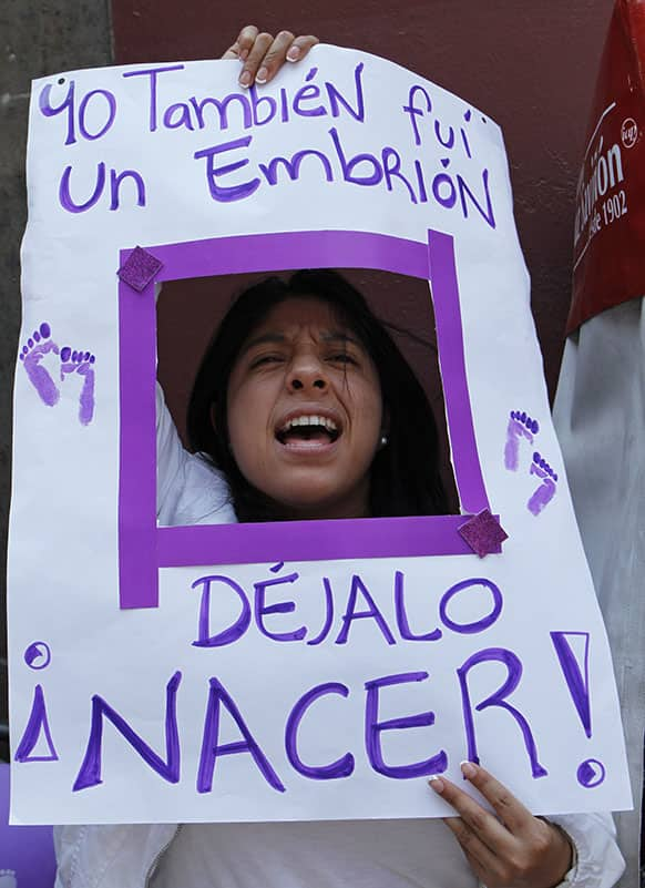 An anti-abortion activist yells through a poster that reads in Spanish