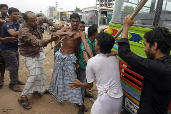 Bangladeshi garment workers beat a driver, for not stopping a bus he was driving, during a protest against the collapse of an eight-storey building that housed several garment factories and poor working conditions of the employees, in Dhaka.