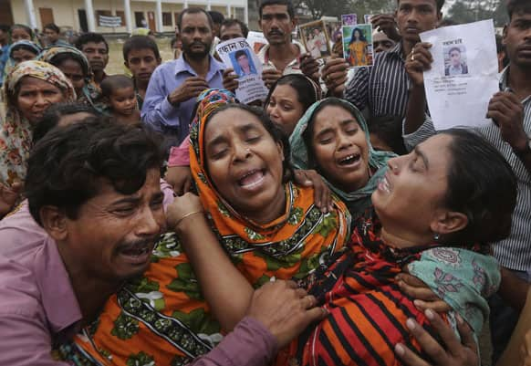 Bangladeshi relatives of garment worker Mohammed Abdullah cry as they as they arrive to collect his body at a makeshift morgue in a schoolyard near a building that collapsed Wednesday in Savar, near Dhaka, Bangladesh.