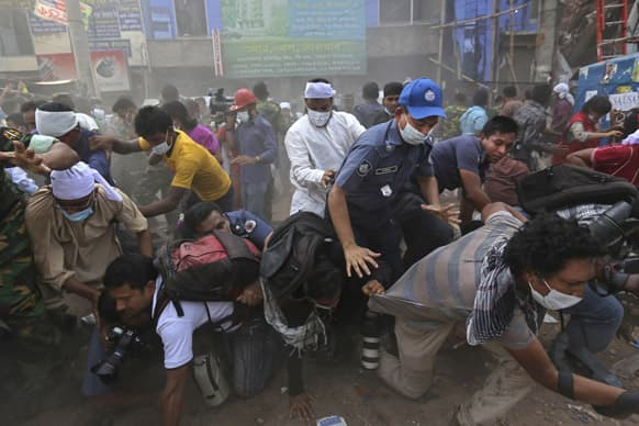 Bangladeshi rescue workers and media fall on top of each other in a stampede after the crowd panic when someone shouted a section of building might collapse, at the site of a building that collapsed Wednesday in Savar, near Dhaka, Bangladesh.