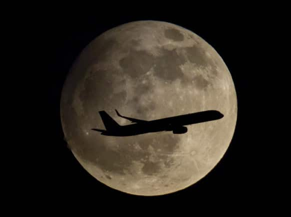 A passenger airplane is about to land at the airport in Frankfurt, Germany, thereby passing the moon which is clearly visible at night.