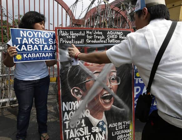 A student spray-paints a mock magazine cover photo of Philippine President Benigno Aquino III heralding him as one of 100 Most Influential Leaders of the World during a rally near the Presidential Palace in Manila, Philippines.