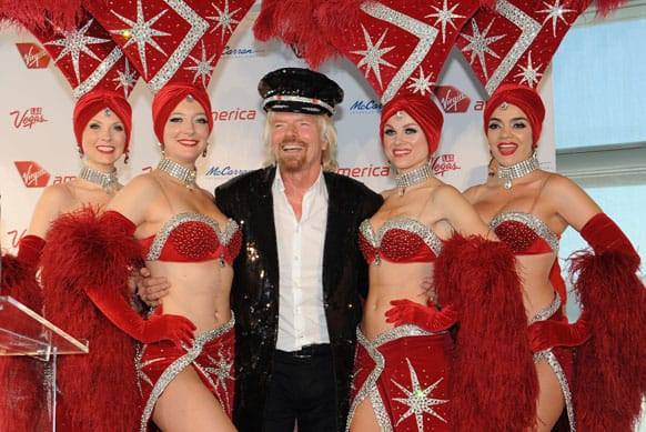 Virgin Group Founder Sir Richard Branson poses for a photo after being presented a sequined captain`s jacket by Las Vegas showgirls during the launch of new nonstop service from Los Angeles International (LAX) to Las Vegas McCarran International (LAS) Airport.