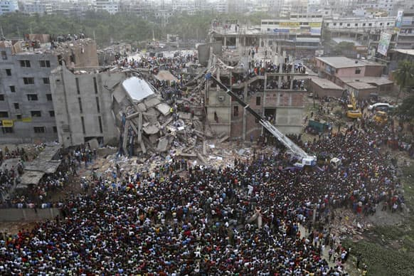 Bangladeshis watch the rescue operations at the site of a building that collapsed Wednesday in Savar, near Dhaka, Bangladesh.