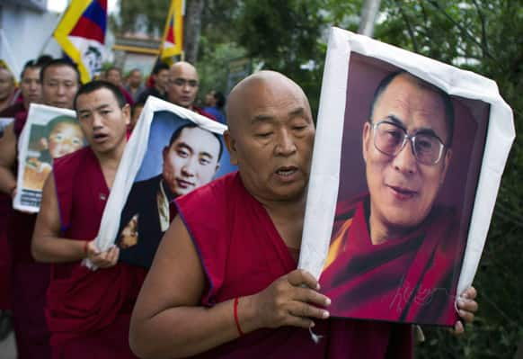 An exiled Tibetan Buddhist monk carries a portrait of spiritual leader the Dalai Lama during a candlelit protest gathering in Dharmsala.