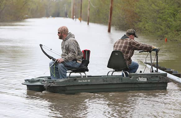 Kevin Eastman, left, prepares his bow for fishing on the flooded Missouri Highway 94 just outside of West Alton, Mo., as his brother, Sean Eastman, right, both of Ferguson, Mo., fights to keep the strong current from pressing their boat against the guardrail.