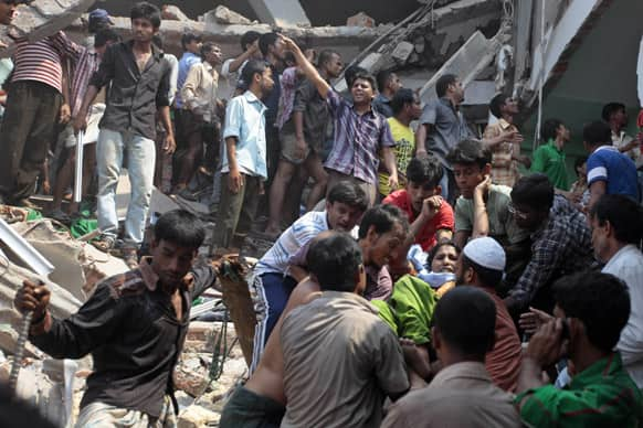A woman, facing the camera on right, who was trapped in a collapsed eight-story building housing several garment factories, is recued in Savar, near Dhaka, Bangladesh.