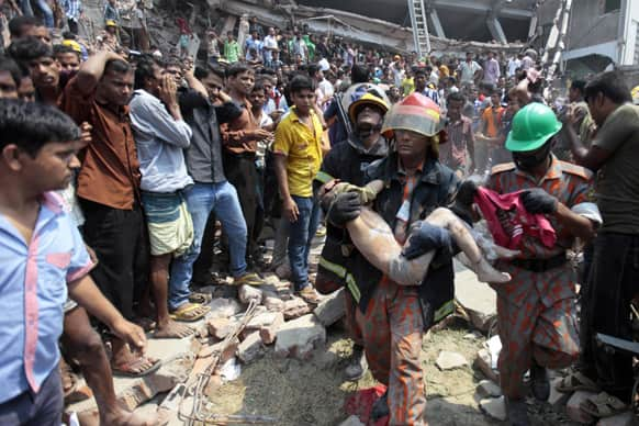 Rescue workers carry a young victim`s body after an eight-story building housing several garment factories collapsed in Savar, near Dhaka, Bangladesh.