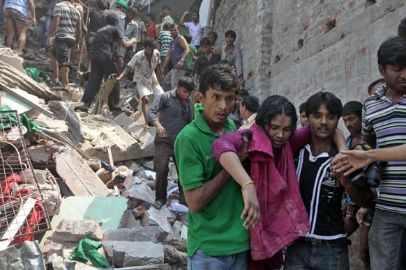 Rescuers assist an injured woman after an eight-story building housing several garment factories collapsed in Savar, near Dhaka, Bangladesh.