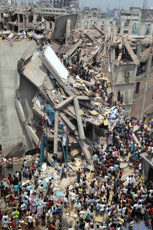 People and rescuers gather after an eight-story building housing several garment factories collapsed in Savar, near Dhaka, Bangladesh.