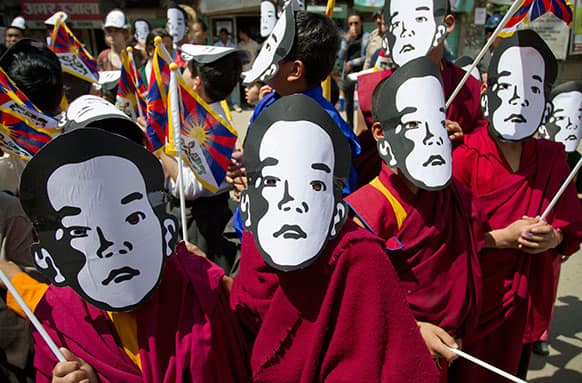 Young exile Tibetan Buddhist monks carry Tibetan flags and wear masks of the Tibetan Buddhist leader Panchen Lama during a protest gathering demanding his release the day before his birthday in Dharmsala.