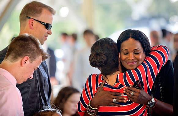 Tameka Foster, mother of Kile Glover, the stepson of R&B artist Usher who died in a boating accident last year, embraces Tara Prince, the mother of Jake and Griffin Prince, as husband Mike Prince and their son Ryan, look on before the signing of a comprehensive boating safety bill.