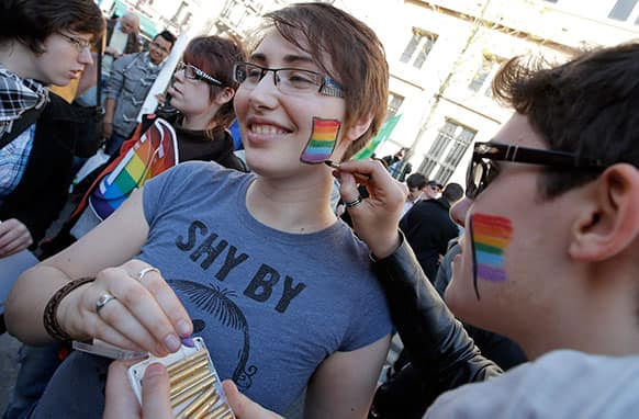 Pro gay marriage activists paint gay colors on their cheeks after French lawmakers legalized same-sex marriage, in Paris.