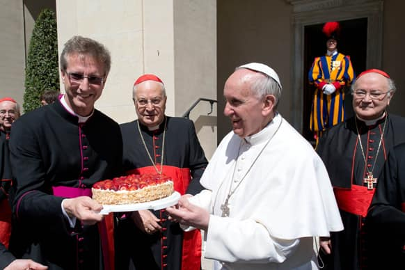 This photo provided by the Vatican paper L` Osservatore Romano, Pope Francis is presented with a cake by the Swiss Guards chaplain Alain de Raemy on the occasion of a celebration for the feast of Saint George, his namesake, at the Vatican.