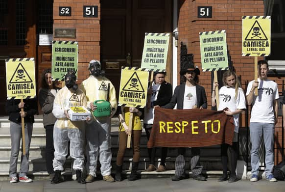Environmental activists, some wearing gas masks and holding placards, demonstrate outside Peru`s embassy in London.