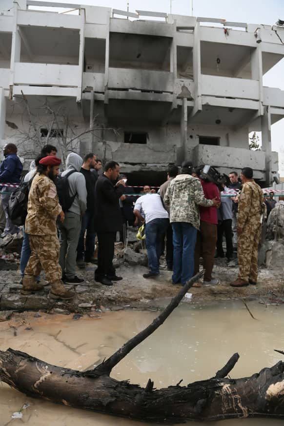 Security personnel and journalists inspect the site of a car bomb that targeted the French embassy wounding two French guards and causing extensive material damage in Tripoli, Libya.