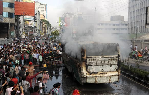 Bangladeshi fire fighters try to douse the fire on a bus set ablaze during a protest by opposition activists in Dhaka, Bangladesh.