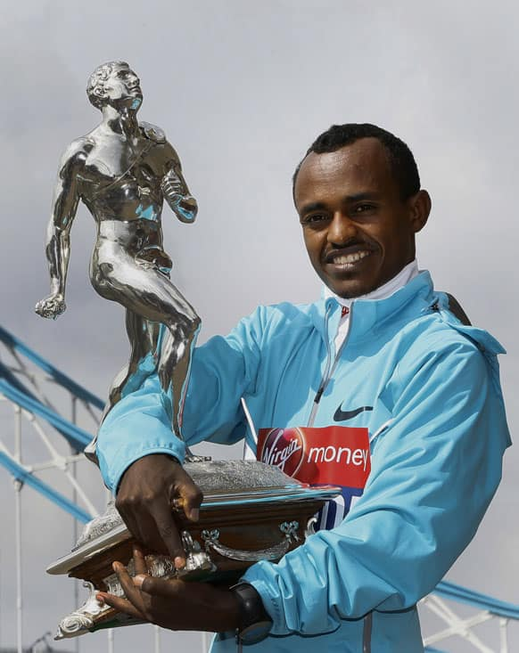 Winner of the men`s 2013 London Marathon Tsegaye Kebede of Ethiopia holds the trophy at a photocall by Tower Bridge in London.