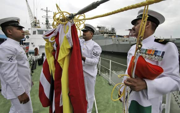 Coast Guard personnels check flags prior to a ceremony at commissioning of a high speed inshore patrol vessel at Rajdood in Kolkata. The ship has maximum speed of 34 knots with water jet propulsion, fitted with a 30 mm gun on front deck, a press release said.