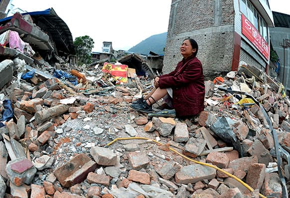 A woman whose relatives were killed in Saturday`s earthquake cries while sitting on a pile of rubble in Lingguan township in Baoxing county of southwest China`s Sichuan province.