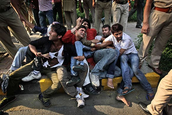 Indian protestors huddle together and shout slogans as police try to remove them from outside the prime minister`s residence during a protest against the rape of a 5-year-old girl in New Delhi.