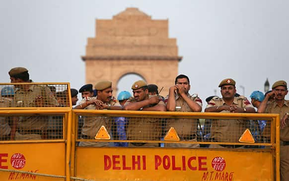 Indian policemen stand behind barricades to block protesters against the rape of a 5-year-old girl near the India Gate monument in New Delhi.