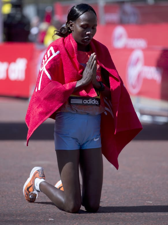 Priscah Jeptoo prays after she won the women`s London Marathon in the Mall, in London.