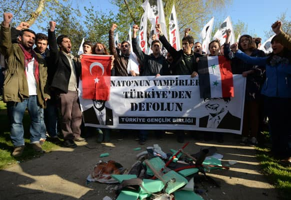 Turks shout slogans with destroyed effigies of U.S. Secretary of State John Kerry and his Turkish counterpart Ahmet Davutoglu as the