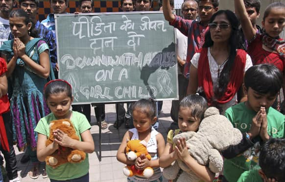 Young girls join others as they pray for the speedy recovery of a 5-year-old girl who was raped and tortured in Delhi.