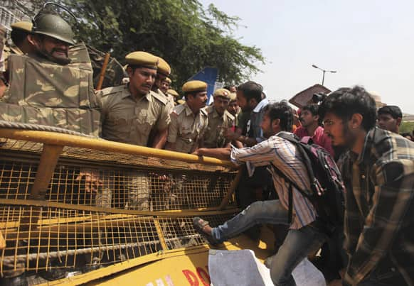 Protesters try to pull down a police barricade outside the Delhi Police headquarters during a protest against the rape of a 5-year-old girl in New Delhi.