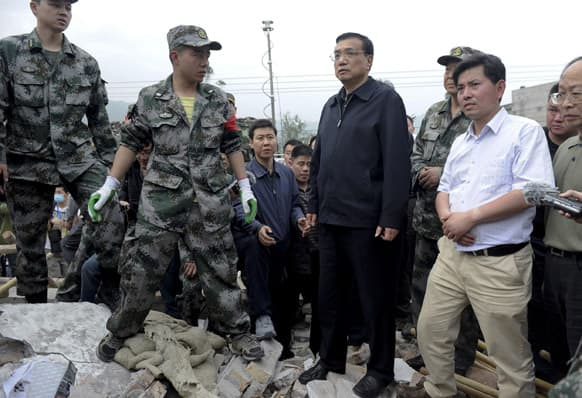 Chinese Premier Li Keqiang, center, is escorted by officials and rescuers as he visits a site damaged by an earthquake at a village in Lushan county, Ya`an, southwest China`s Sichuan province.