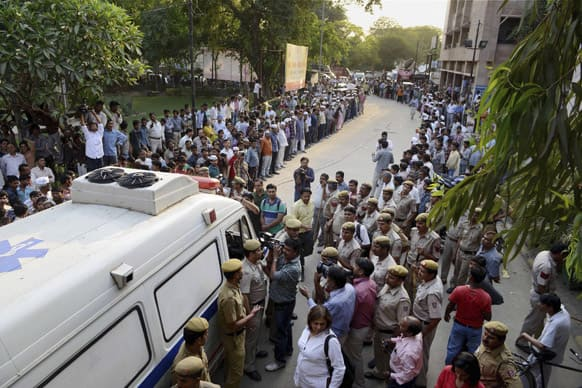 People watch an ambulance carrying a 5-year-old girl to a hospital for treatment after she was raped and tortured in New Delhi.