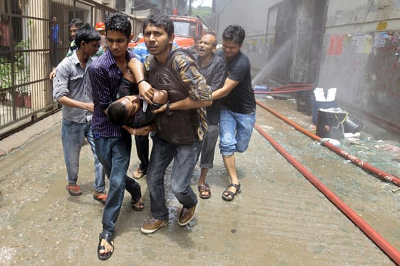 Volunteers rescue an injured man from a shopping mall that caught fire in Dhaka, Bangladesh. The fire was reportedly caused by a gas cylinder explosion.