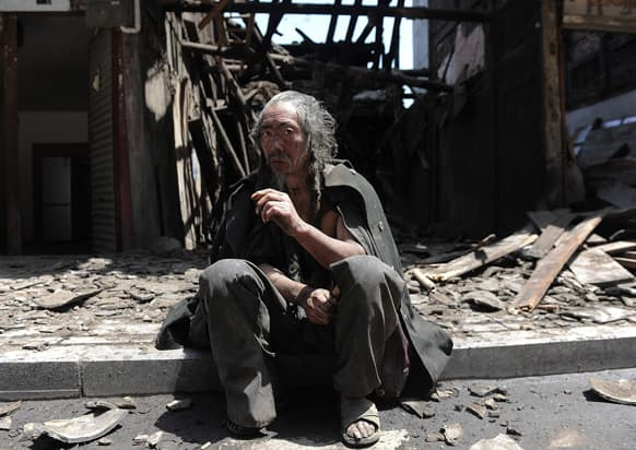 A man sits in front of the houses destroyed by an earthquake which hit Lushan county in Ya`an in southwest China`s Sichuan province.