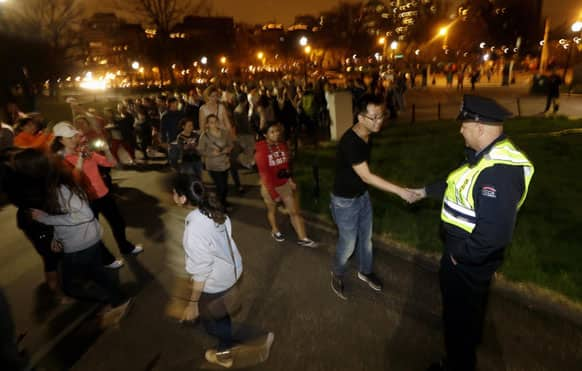 A line forms to shake the hand of officer Raymond Coldero, right, as a crowd reacts to news of the arrest of one of the Boston Marathon bombing suspects during a celebration at Boston.