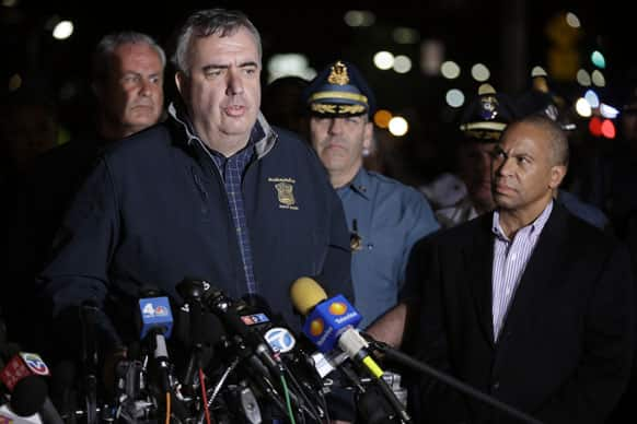 Boston Police Commissioner Ed Davis, at podium, speaks while accompanied by State Police Col. Timothy Alben, second from right, and Massachusetts Governor Deval Patrick, right, during a news conference, after the arrest of a suspect of the Boston Marathon bombings in Watertown.