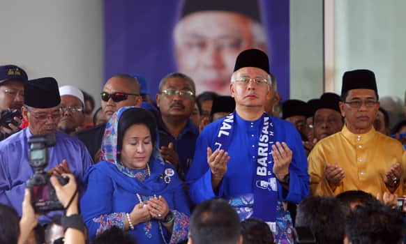 Malaysian Prime Minister Najib Razak and his wife Rosmah Mansor, offer prayers before leaving for an election nomination center in Pekan, Pahang state, Malaysia.