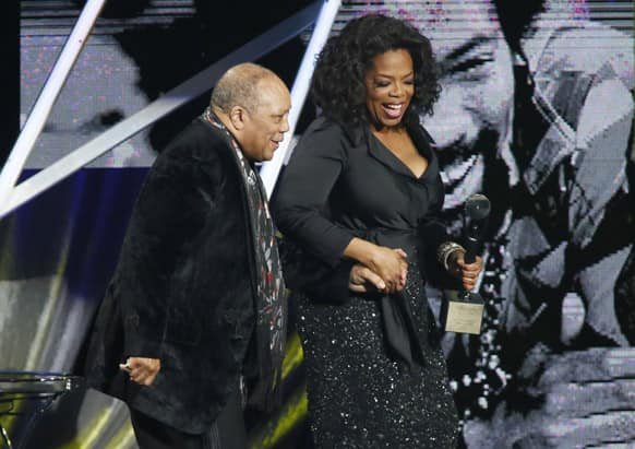Oprah Winfrey, right, leads Quincy Jones, left, on the stage after speaking to induct him into the Rock and Roll Hall of Fame during the Rock and Roll Hall of Fame Induction Ceremony at the Nokia Theatre.