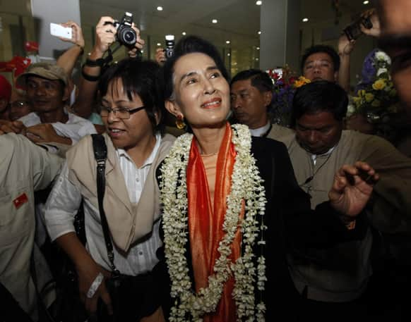 Myanmar opposition leader Aung San Suu Kyi is greeted by supporters at Yangon International Airport upon returning from Japan.