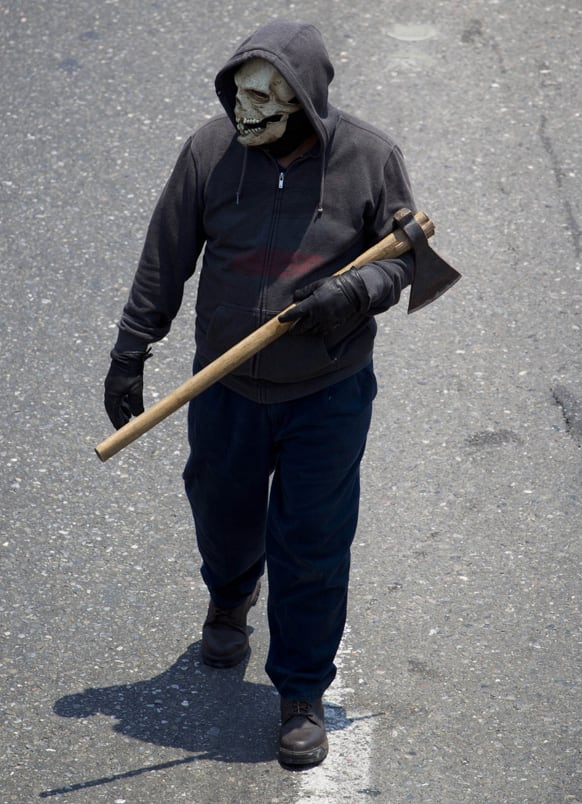 A masked teacher hold an axe blocks a major highway during a protest in Chilpancingo, Mexico.