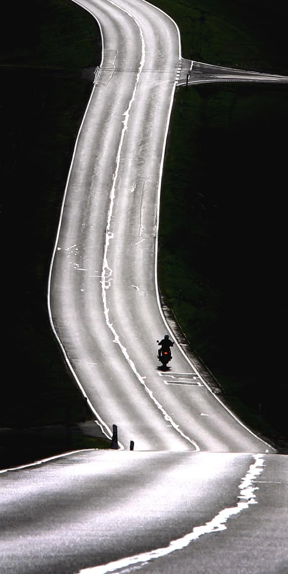 A motorcyclist rides along the street which is illuminated by the sun near Remlingen, Germany.