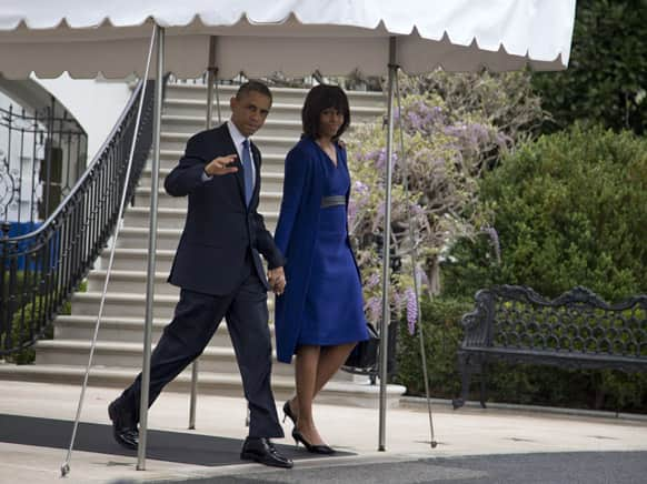 Barack Obama, accompanied by Michelle Obama, waves to media as they leave the White House to board the Marine One helicopter, en route to Andrews Air Force Base and onto Boston where they will attend a service dedicated to those who were gravely wounded or killed in the bombing.